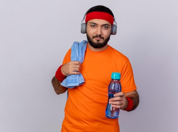 Junger sportlicher mann, der kamera betrachtet, die stirnband und armband mit kopfhörern hält wasserflasche an kamera mit handtuch auf schulter lokalisiert auf weißem hintergrund hält