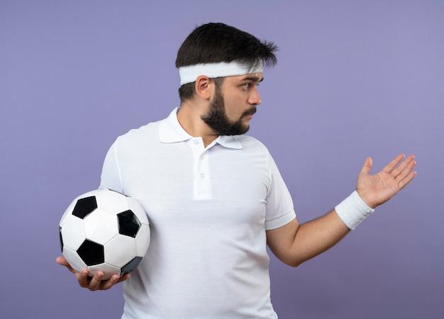 Junger sportlicher mann, der seite betrachtet, die stirnband und armband hält ball hält und hand an seite hält