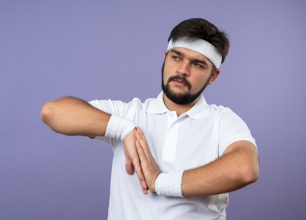 Junger sportlicher mann, der seite betrachtet, die stirnband und armband hält, die hände zusammen lokalisiert auf grüner wand halten