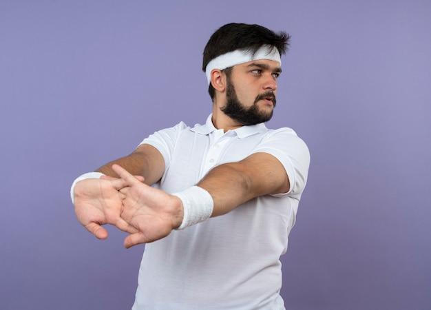 Junger sportlicher mann, der seitliches tragen des stirnbandes und des armbandes betrachtet, das arm lokalisiert auf grüner wand ausdehnt