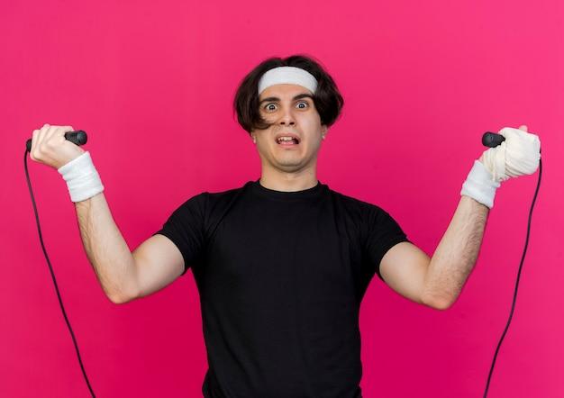 Junger sportlicher mann, der sportbekleidung und stirnband hält, das springseil hält, das verwirrt geht, um zu springen