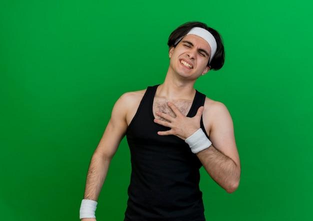 Junger sportlicher mann, der sportbekleidung und stirnband hält, die hand auf brustgefühlsschmerz halten