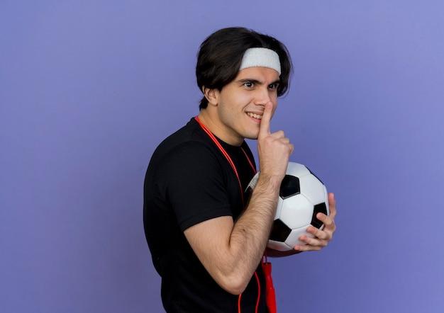 Junger sportlicher mann, der sportbekleidung und stirnband mit springseil um den hals hält, der fußball macht, der stille geste mit finger auf lippen macht