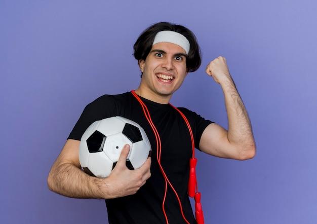 Junger sportlicher mann, der sportbekleidung und stirnband mit springseil um den hals hält, der fußballball ballend faust glücklich und aufgeregt hält