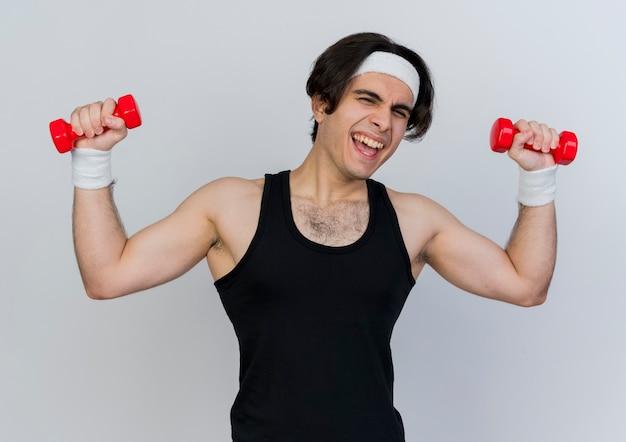 Junger sportlicher mann, der sportbekleidung und stirnband trägt, die mit glücklichen und aufgeregten hanteln arbeiten, die über weißer wand stehen