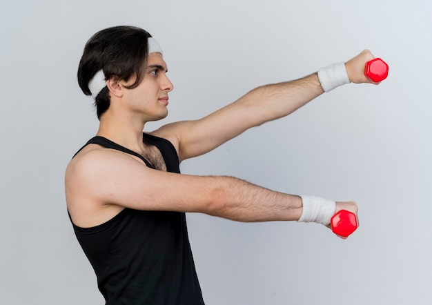 Junger sportlicher mann, der sportbekleidung und stirnband trägt, die mit hanteln arbeiten, die mit glücklichem gesicht lächeln über weißer wand arbeiten