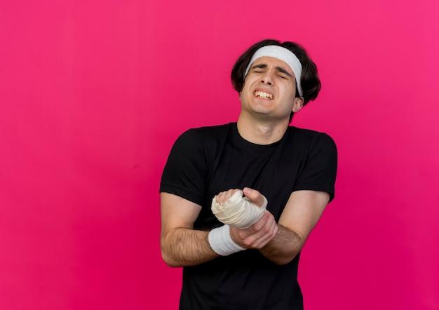 Junger sportlicher mann, der sportbekleidung und stirnband trägt, die sein verbundenes handgelenk berühren, das unter schmerzen leidet