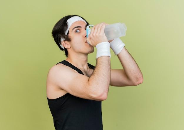 Junger sportlicher mann, der sportkleidung und stirnbandtrinkwasser nach dem training trägt
