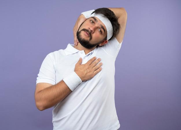 Junger sportlicher mann, der stirnband und armband trägt -