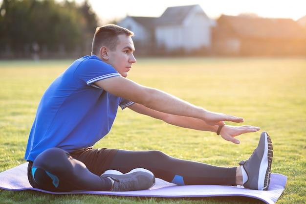 Junger sportlicher mann, der streckübungen vor dem laufen im morgenfeld im freien tut.