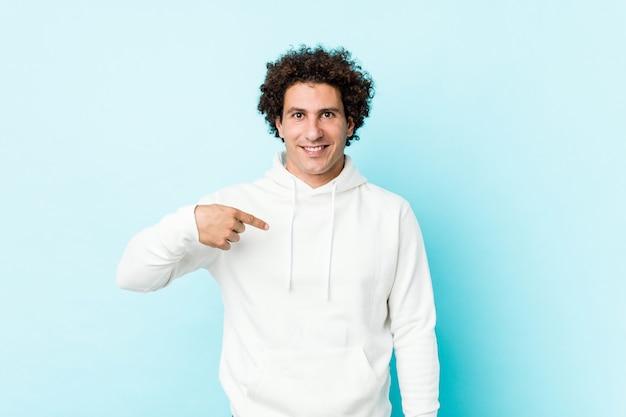 Junger sportlicher mann gegen eine blaue hintergrundperson, die eigenhändig auf einen hemdkopienraum, stolz und überzeugt zeigt