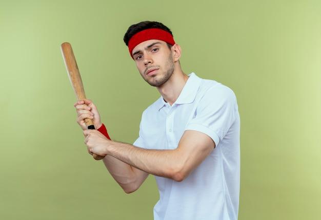 Junger sportlicher mann im schwingenden baseballschläger des stirnbandes, der kamera mit ernstem gesicht betrachtet, das über grünem hintergrund steht