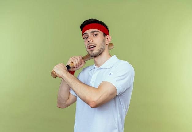 Junger sportlicher mann im stirnband, der baseballschläger mit sicherem ernstem ausdruck hält, der über grüner wand steht