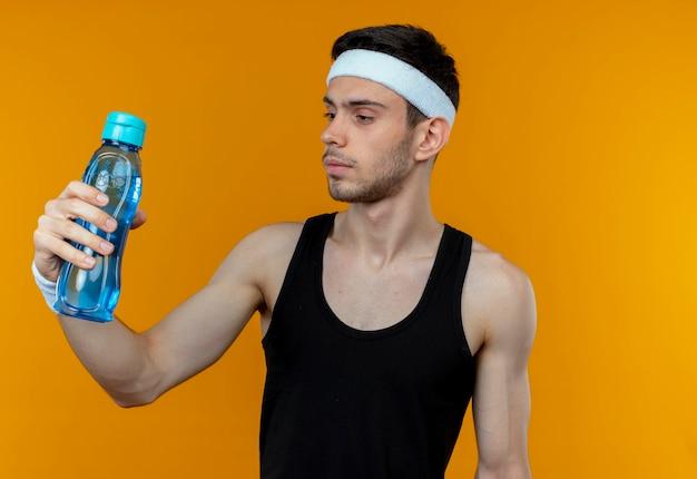Junger sportlicher mann im stirnband, der eine flasche wasser hält, schaut es mit ernstem gesicht an, das über orange wand steht