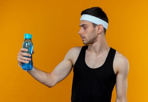 Junger sportlicher mann im stirnband, der flasche wasser hält, das es mit ernstem gesicht betrachtet, das über orange hintergrund steht