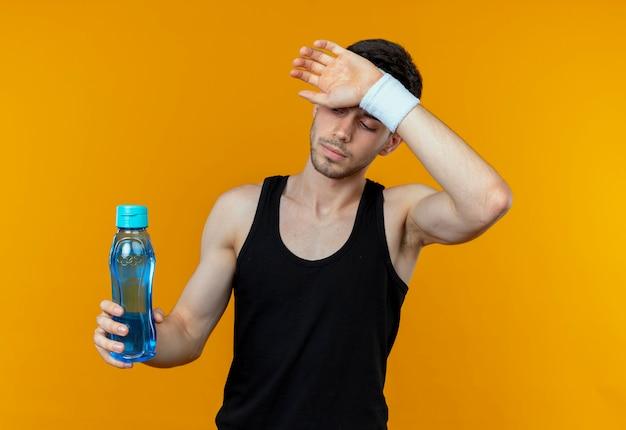 Junger sportlicher mann im stirnband, der flasche wasser hält, der müdigkeit fühlt, die über orange wand steht