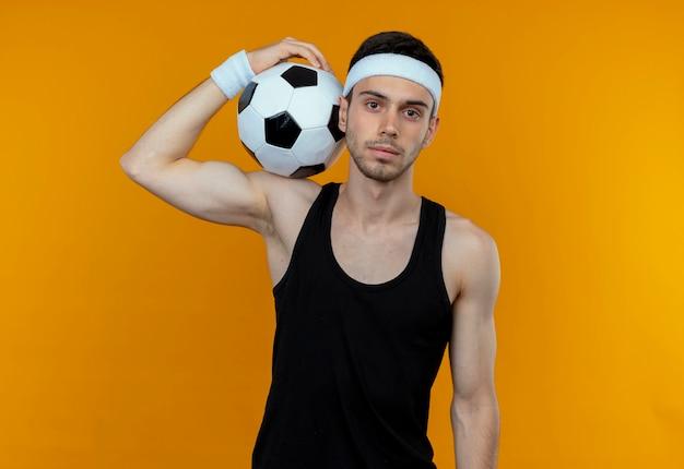 Junger sportlicher mann im stirnband, der fußball auf seiner schulter mit sicherem ernstem ausdruck hält, der über orange wand steht