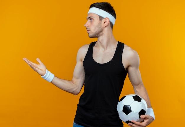 Junger sportlicher mann im stirnband, der fußball hält, der beiseite mit arm heraus schaut, als fragend oder streitend über orange wand