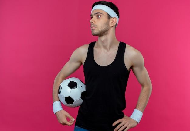 Junger sportlicher mann im stirnband, der fußball hält, der beiseite mit ernstem gesicht steht über rosa wand steht