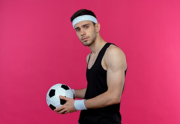 Junger sportlicher mann im stirnband, der fußball mit ernstem ausdruck hält, der über rosa wand steht