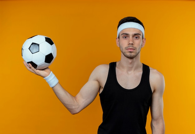 Junger sportlicher mann im stirnband, der fußball mit sicherem ernstem ausdruck hält, der über orange wand steht