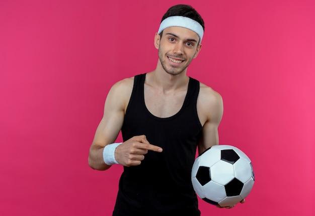 Junger sportlicher mann im stirnband, der fußball zeigt, der mit zeigefinger zum ball zeigt, der glücklich und positiv über rosa wand steht