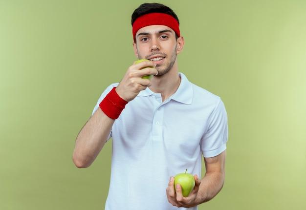 Junger sportlicher mann im stirnband, der grüne äpfel hält, die einen über grün beißen