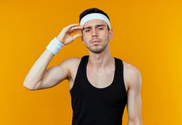 Junger sportlicher mann im stirnband, der kamera betrachtet, die seinen kopf müde und gelangweilt über orange hintergrund stehend berührt