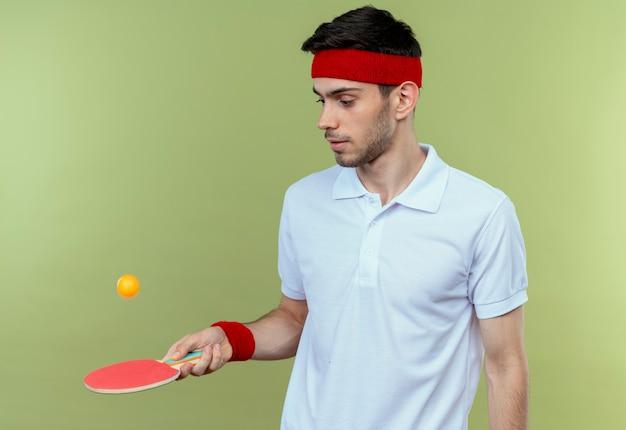 Junger sportlicher mann im stirnband, der schläger für tischtennis hält, der einen ball wirft, der über grüner wand steht