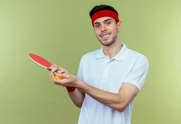 Junger sportlicher mann im stirnband, der schläger und ball für tischtennis betrachtet, die kamera lächelnd steht über grünem hintergrund