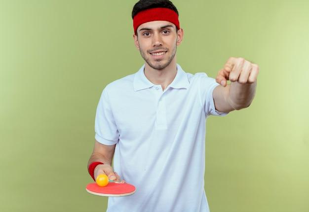 Junger sportlicher mann im stirnband, der schläger und ball für tischtennis betrachtet, die kamera lächelnd zeigt mit zeigefinger auf sie steht über grünem hintergrund