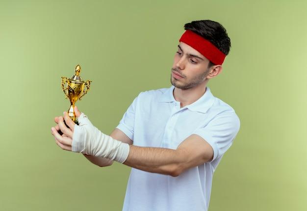 Junger sportlicher mann im stirnband, der seine trophäe hält, die es mit sicherem ausdruck betrachtet, der über grünem hintergrund steht