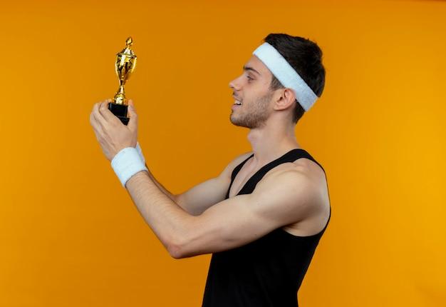 Junger sportlicher mann im stirnband, der seine trophäe hält, die ithappy und positives lächelndes stehen über orange hintergrund betrachtet