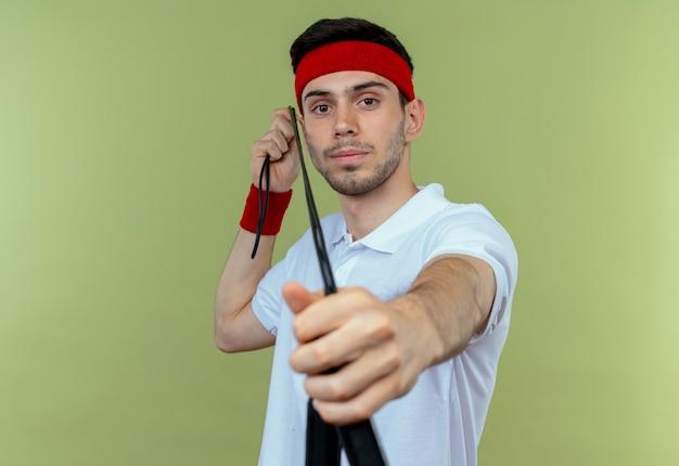 Junger sportlicher mann im stirnband, der springseil hält, wie mit pfeil und bogen über grün zielt