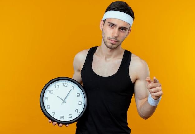 Junger sportlicher mann im stirnband, der wanduhr hält, zeigt mit missfallenem finger, der über orange wand steht