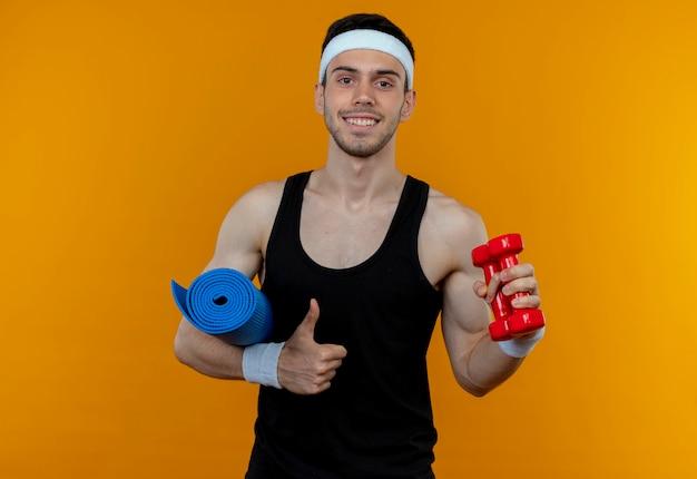Junger sportlicher mann im stirnband, der yogamatte und hantel hält, zeigt daumen hoch lächelnd fröhlich stehend über orange wand