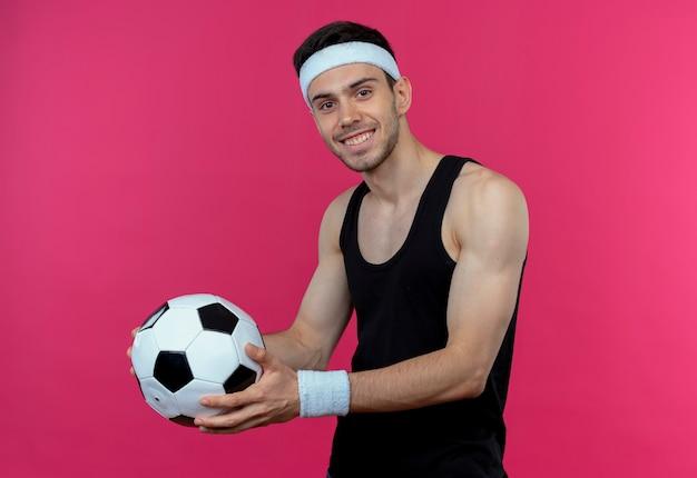 Junger sportlicher mann im stirnband hält fußball lächelnd, der fröhlich über rosa wand steht
