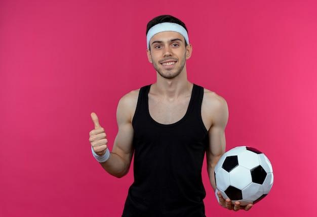 Junger sportlicher mann im stirnband hält fußball lächelnd und zeigt daumen hoch stehend über rosa wand
