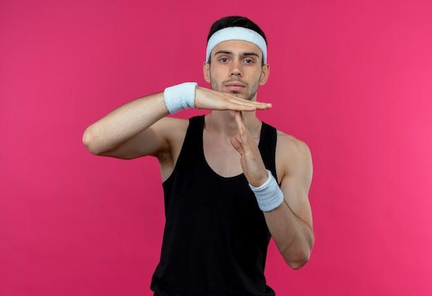 Junger sportlicher mann im stirnband mit ernstem gesicht, das auszeitgeste mit händen über rosa zeigt
