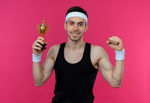 Junger sportlicher mann im stirnband mit goldmedaille um hals hält trophäe, die faust hebt und lächelnd über rosa wand steht