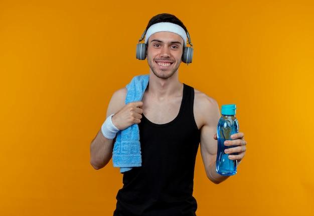 Junger sportlicher mann im stirnband mit handtuch auf schulter, die flasche wasser betrachtet, die kamera lächelnd steht über orange hintergrund