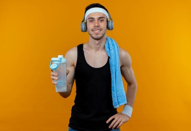 Junger sportlicher mann im stirnband mit handtuch auf schulter, die flasche wasser mit lächeln auf gesicht über orange hält