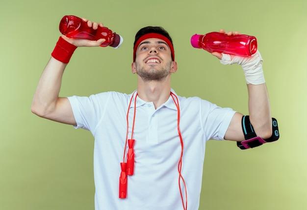 Junger sportlicher mann im stirnband mit springseil um den hals, der zwei flaschen wasser über grün hält