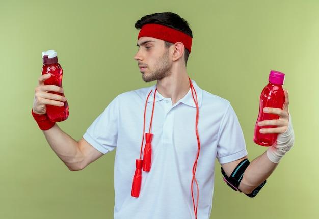 Junger sportlicher mann im stirnband mit springseil um den hals hält zwei flaschen wasser, die verwirrt schauen und versuchen, wahl über grün zu treffen