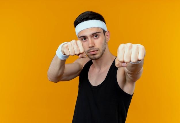 Junger sportlicher mann in der geballten faust des stirnbandes, die zur kamera steht, die über orange hintergrund steht