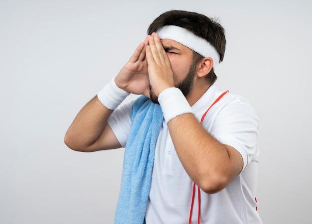 Junger sportlicher mann mit geschlossenen augen, die stirnband und armband mit handtuch und springseil auf schulter tragen, die jemanden lokalisiert auf weißer wand nennt