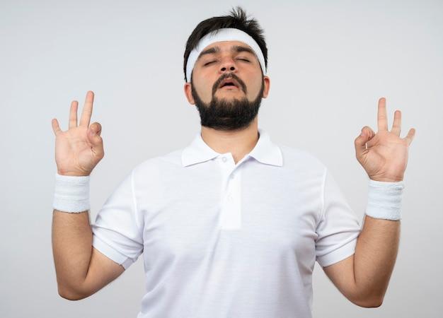 Junger sportlicher mann mit geschlossenen augen, die stirnband und armband tragen, die meditationsgeste zeigen, die auf weißer wand lokalisiert wird