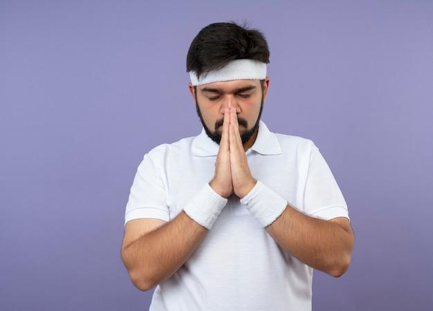 Junger sportlicher mann mit geschlossenen augen, die stirnband und armband tragen gebetsgeste zeigen