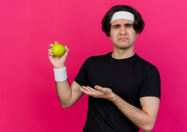 Junger sportlicher mann mit sportkleidung und stirnband, der einen grünen apfel hält und ihn mit traurigem gesichtsausdruck präsentiert