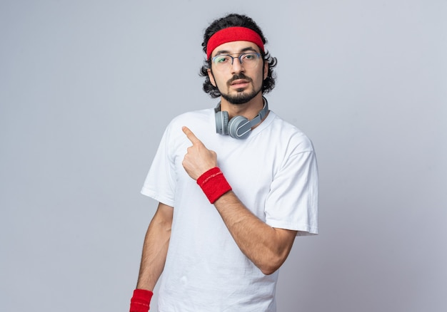 Junger sportlicher mann mit stirnband mit armband und kopfhörern an den nackenpunkten an der seite
